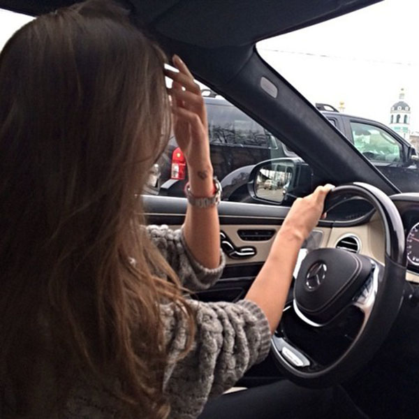 Girl fixing her hair in car